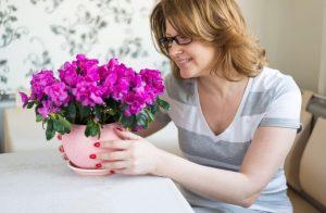 Саксийни цветя за Скорпион - жена, държаща гърне с азалии